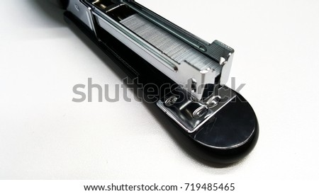 Stapler and staple. Big black stapler with metal staple isolated on white background. Closeup top view. Office supplies equipment concept.