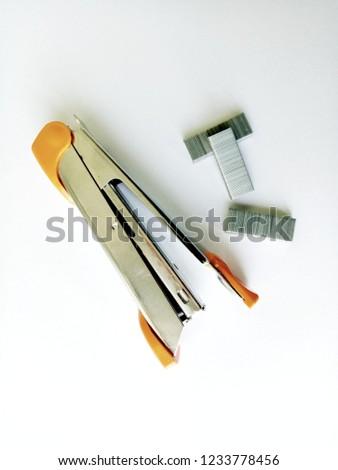 Stapler and staples over white, stapler machine on the table.