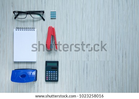 stapler, hole punch, calculator on light wood, light background, flat lay