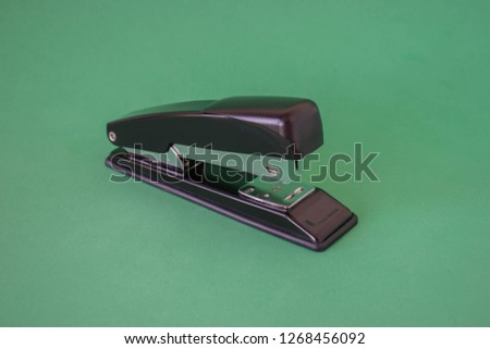 Stapler on a green background