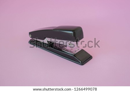 Stapler on a pink background