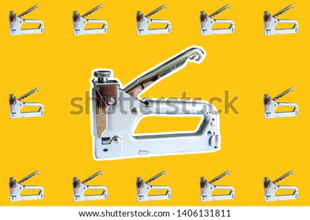 Stapler on an orange background and small staplers as a background texture