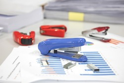 Stapler on the desk with paper documents. Office essential tools for paperwork