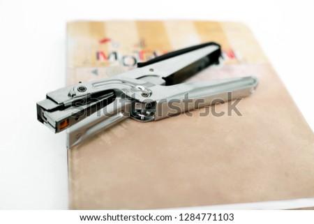 Stapler on the diary. Isolated on the white background.