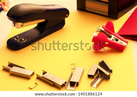 stapler, paper clips, anti stapler on the desktop on the background of stickers and folders in isolation