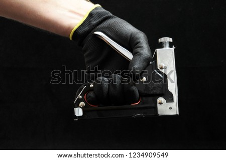Stapler Pliers and a Hand on a Black Background