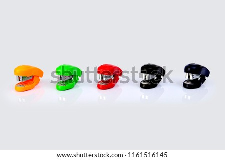 Staplers of different colors isolated on a white background.