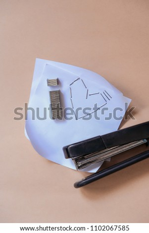 staples and stapler. composition with stapler, brackets and sheet of paper. creative concept for stationery. soft selective focus.
