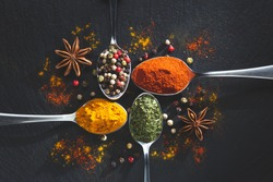 Star anis and spoons with pepper, paprika, parsley and turmeric on black background with copy space, top view. Cooking ingredients and condiments concept.