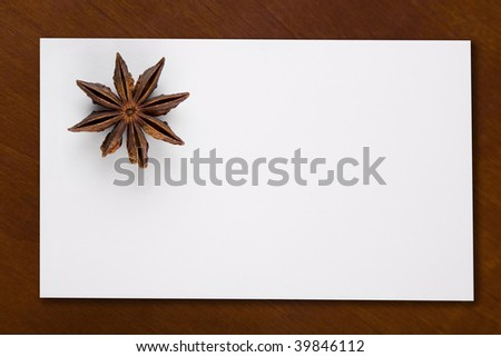 Star Anis on a white invitation card on a wooden table