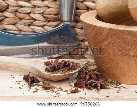 Star anise and cumin seed herbs in kitchen setting with rustic wooden utensils