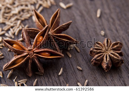 Star anise and cumin seeds on a wooden board