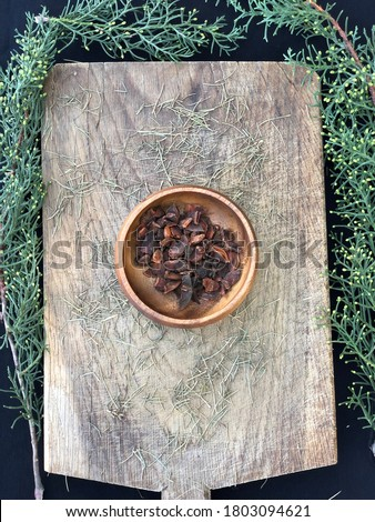Star anise (Illicium verum) in brown wooden bowl with pine leaves on wood (yildiz anason in Turkish) Stok fotoğraf ©
