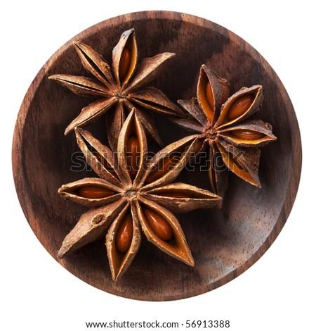 Star anise in a small wooden dish, isolated on white.  Overhead view.
