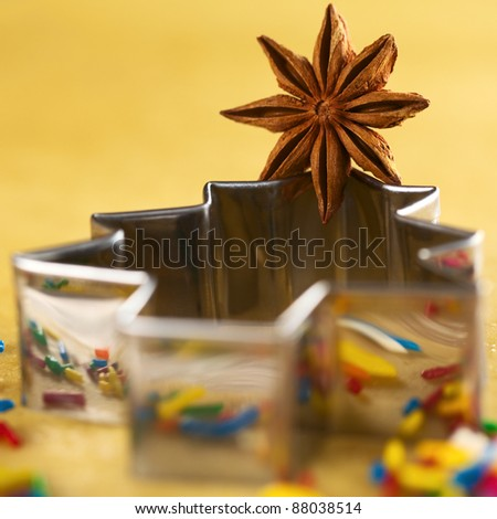 Star anise on Christmas tree shaped cookie cutter lying on dough (Selective Focus, Focus on the middle of the anise) - stock photo