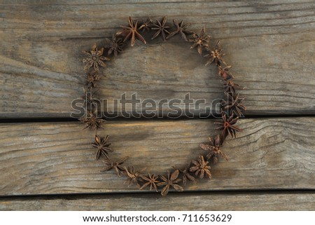 Star anises arranged in circle shape on wooden table