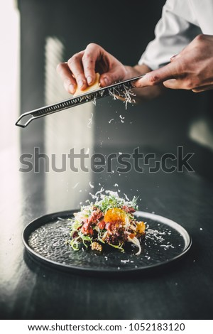 star chef grate cheese on top of fresh food on dark table