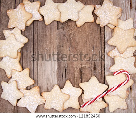 Star Christmas cookies and candy canes on wooden background