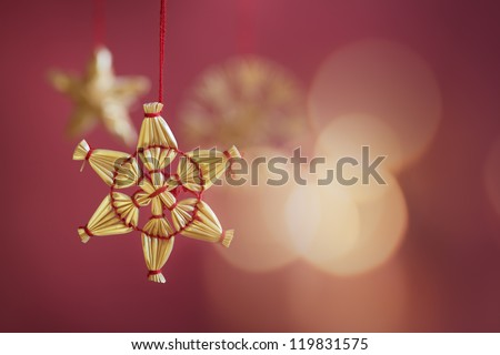 Star christmas tree decoration on red background with glitters of candle