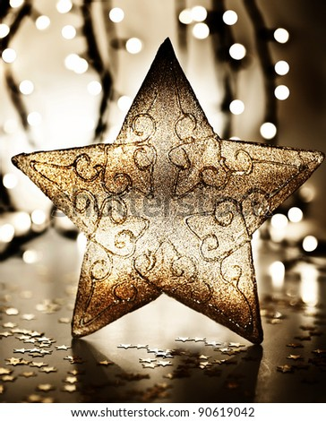 Star, Christmas tree ornament, golden decoration over blur lights, dark new Year eve background, winter holidays home decor
