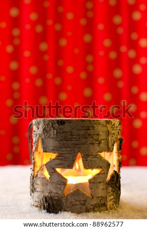 Star jar candle holder in snow on a red golden background - stock photo