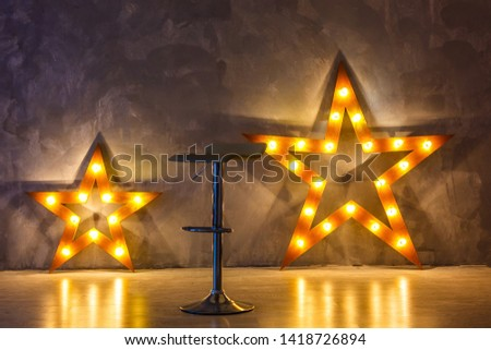 Star lamp on the background of an old wall, on the wooden floor, lights, lights, lights, glare. Exhibition star, light object, interior decor. Abstract dark background, night view, club #1418726894