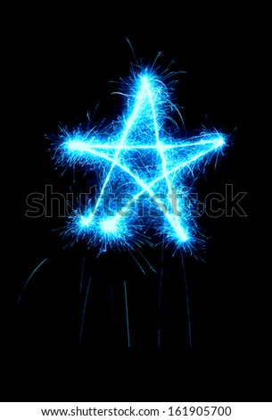 Star made by sparkler isolated on black background. Christmas, holiday, celebration symbol.
