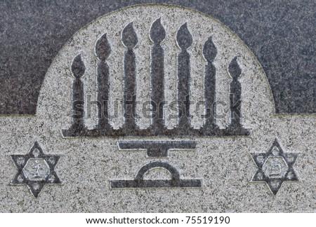 Star of David and menorah on granite tombstone. Old Jewish cemetery in California