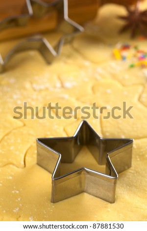 Star-shaped cookie cutter and other Christmas shapes cut into dough (Selective Focus, Focus on the two front edges of the star-shaped cutter)