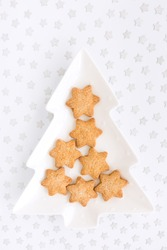 Star shaped homemade Christmas biscuits on tree shaped plate and silver star confetti on white background with copy space. Top view.