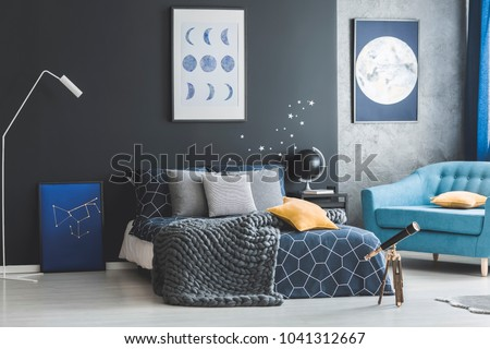 Star stickers on dark wall above bed near telescope in bedroom interior with gallery of posters