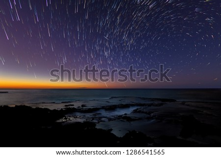 Star trails at dusk over a lava table from the west coast of Oahu, Hawaii, Keana Point with a meteor