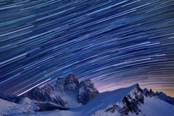 Star trails over the mountains, Dolomites, Italy.  Beautiful spiral star trail at night. Fantastic star timelapse with mountain background.  Christmas time, Cortina Happy new year