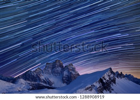Photo of  Star trails over the mountains, Dolomites, Italy.  Beautiful spiral star trail at night. Fantastic star timelapse with mountain background.  Christmas time, Cortina Happy new year