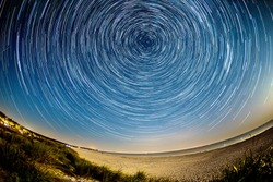 star trails over the nightly beach