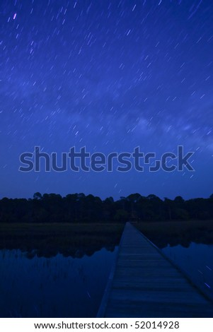 star trails over water and boardwalk