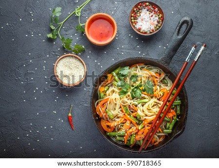 Starch (rice, potato) noodles with vegetables - bell peppers, carrots, green beans, onions, sesame seeds and soy sauce. Vegetarian dish. A delicious dinner in the Asian style