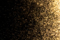 Stardust gold bokeh on black background with flare effect. Glitter golden lighting on dark wall with explosion sparkle on midnight wallpaper concept for Christmas theme or other design.
