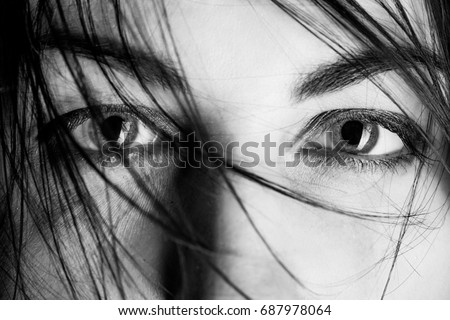 stared female eyes under blowing hair close up