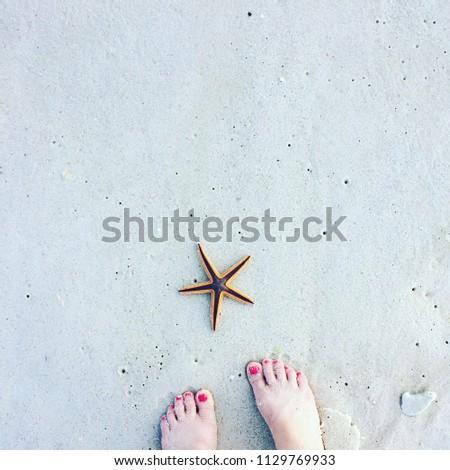 Starfish and Feet at Destin Beach #1129769933