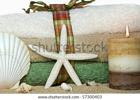 starfish and seashell in sand with towel stack