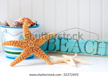 Starfish and wooden beach sign with pail of seashells