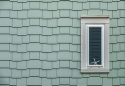 Starfish at bottom of tall narrow window surrounded by grayish shingles on one side of a beach house