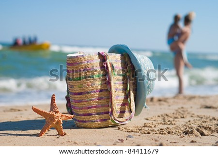 Starfish, beach bag and a woman's hat on the beach.