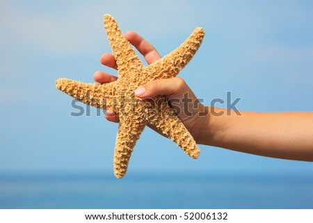 starfish in child's hand. focus on wrist. sea and sky in out of focus.