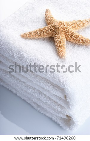 Starfish on stack of white towels with reflection.
