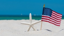 Starfish or Sea Star and American Flag.  4th of July Independence Day. Ocean Beach sand. Summer vacations. Bright sunny day and blue color of salt water. Florida paradise. Tropical nature. Seascape.