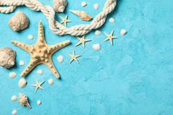 Starfish, rope and seashells on blue background, space for text