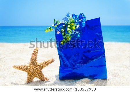 Starfish with blue gift bag on sandy beach in sunny day- holiday concept