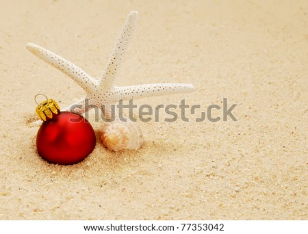 starfish with conch shell and red Christmas ornament on a beach - concept of a warm weather Christmas